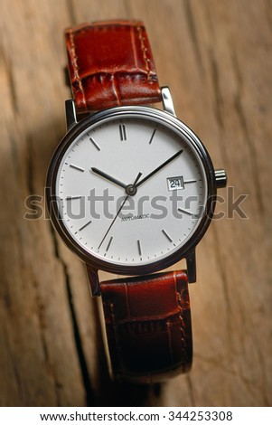 Classic wrist watch over wooden background - stock photo