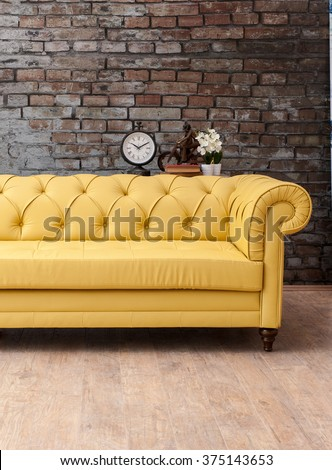 classic yellow sofa living room with brick wall and clock