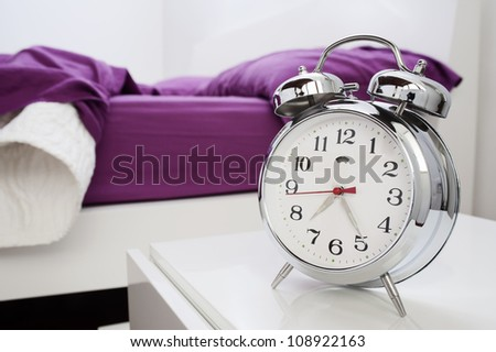 classical alarm clock on bedside table