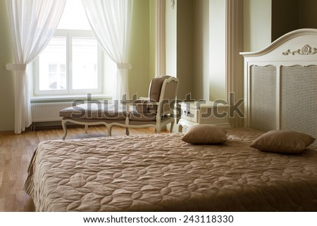 Classical bedroom interior with white curtains, armchair and a bed - stock photo