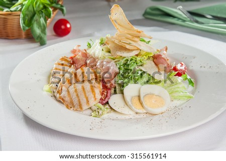 Classical Caesar salad with  roasted chiken, bacon, sliced eggs, lettuce leaves, crackers, parmesan and cherry tomatoes and cream sause on  the white round  plate close up - stock photo