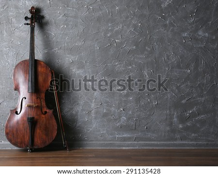 Classical cello and bow on gray wall background - stock photo
