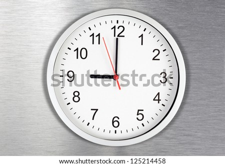 Classical clock on metal background displaying nine o'clock - stock photo