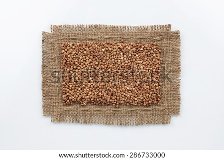 Classical frame made of burlap with grains of buckwheat, on a white background