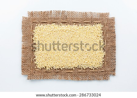 Classical frame made of burlap with grains of millet, on a white background