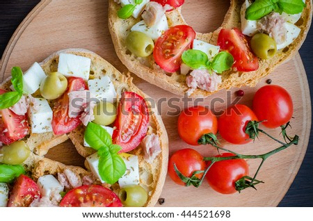 Classical frisella tomato, cheese mozzarella, tuna and olives. Italian starter friselle. Dried bread called freselle on wooden board with tomatoes cherry. Italian food. Healthy vegetarian food. - stock photo