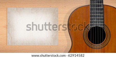Classical guitar on plywood wall with blank page of mulberry paper for your note - stock photo
