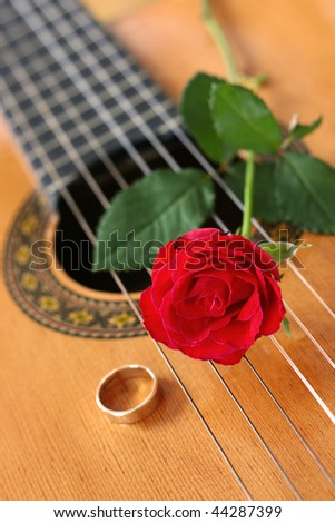 Classical guitar with a red rose and gold ring - stock photo