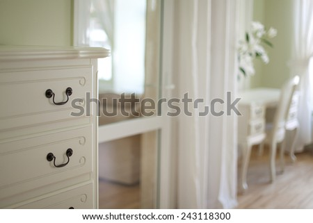 Classical interior, fragment of a bedroom with a white commode - stock photo