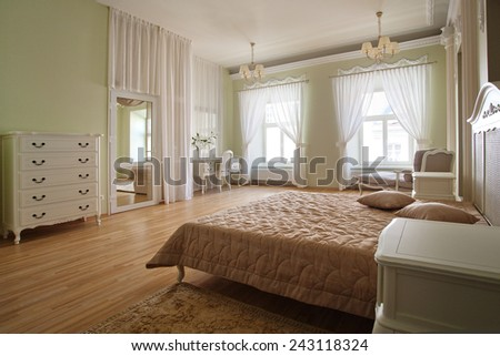 Classical interior of a bedroom with a bed and commode - stock photo