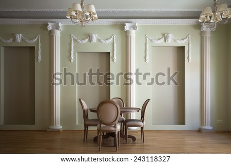 Classical interior of a living room with a round dining table and chairs