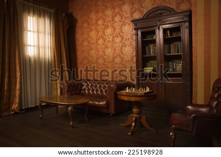 Classical library room with leather armchair, wooden table and bookcase - stock photo