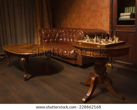 Classical library room with leather couch, wooden table  - stock photo