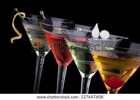 Classical martini in chilled glass over black background on reflection surface, garnished with freah blackberry, maraschino cherry, marinated pearl onoions, olive and lemon twist. - stock photo