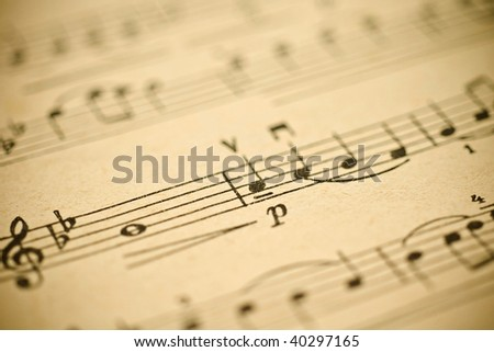 Classical music - notes on yellowed vintage paper sheet (shallow DOF) - stock photo