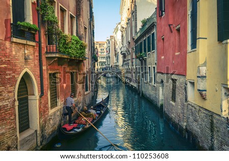 Classical picture of the venetian canals with gondola across the canal. - stock photo