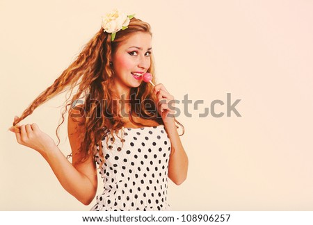 classical pin-up image of a pretty smiling blond girl with a lollipop in her hand. Toned in retro style.