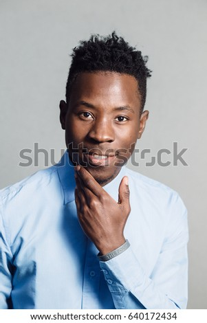 Classical portrait of african american man in blue shirt at grey wall background