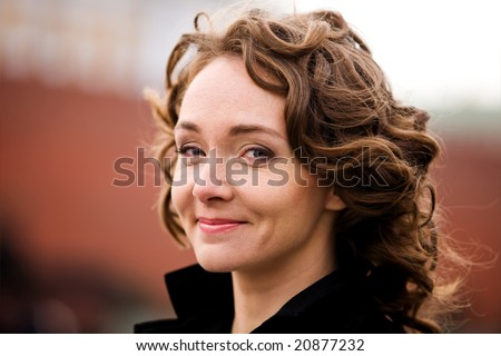 Classical portrait of attractive smiling woman outdoors - stock photo