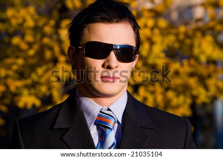 Classical portrait of young businessman in sunglasses outdoors