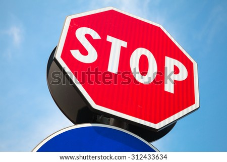 Classical red Stop road sign over blue sky background - stock photo
