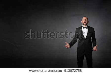 classical singer gestures with hands, dark background