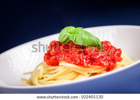 Classical spaghetti with tomato sauce on blue background with basil - stock photo