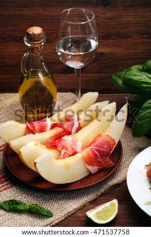 Classical Spanish snacks (tapas) of melon and cured meats (ham) on a brown wooden background. A bottle of olive oil and a glass of water in the background. Fine dining.