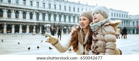 Classical tourist enjoyment in Venice, Italy. happy young mother and daughter in the winter at San Marco square in Venice, Italy pointing at something