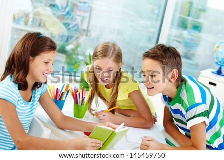 Classmates being curious about what their cute friend reading - stock photo