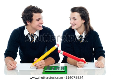 Classmates looking at each other and discussing the correct answer before writing - stock photo