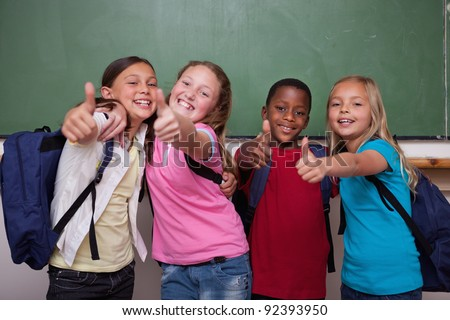 Classmates posing with the thumb up in a classroom - stock photo