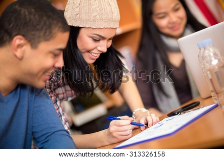 Classmates writing her task after class  - stock photo