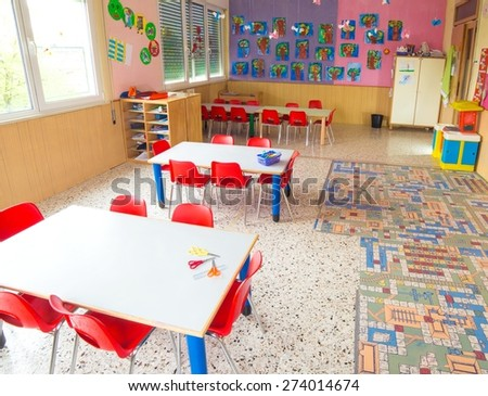 classromm of kindergarten with tables and small red chairs for children - stock photo