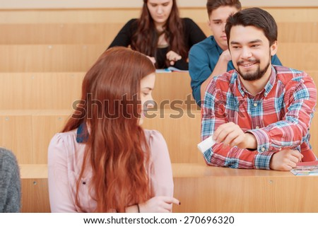 Classroom gossip. Close-up of a young smiling male student passing a paper note to his female classmate sitting ahead in an auditorium