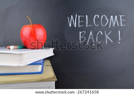 Classroom with apple, books and blackboard with handwriting - stock photo