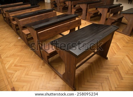 Classroom with parquet floor and rows of old desks. - stock photo