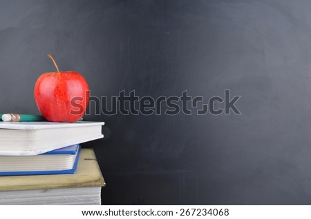 Classroom with red apple, books and blackboard - stock photo