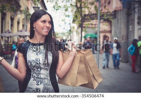 Classy attractive brunette wearing black white dress in urban environment carrying shopping bags and smiling. - stock photo
