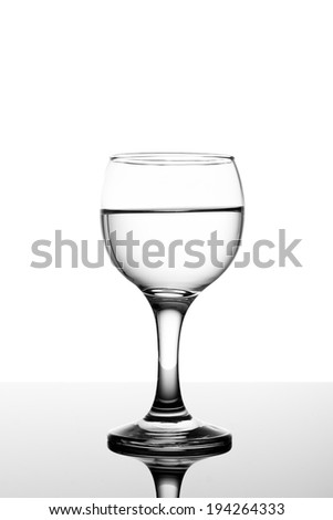 Classy backlit glass of water on white background and reflection
