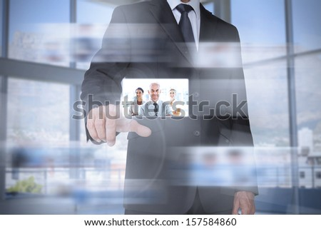 Classy businessman in bright office presenting digital interface showing coworkers - stock photo