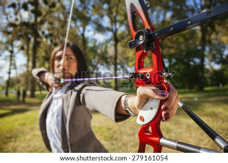 Classy Businesswoman Practicing Archery Outdoors. Focus Is On Bow. - stock photo