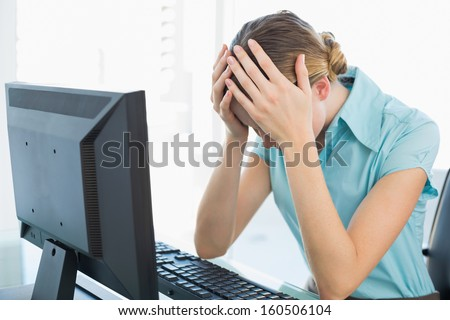Classy frustrated businesswoman working at computer in bright office - stock photo