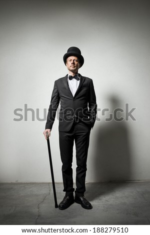 Classy gentleman with bowler hat and cane looking confidently at camera. - stock photo