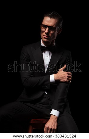 classy man in black suit wearing glasses posing in dark studio background touching his arm and looking away - stock photo