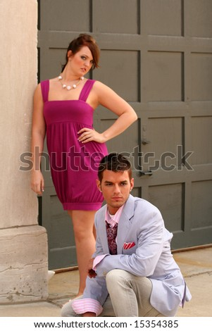 Classy woman and man posing in front of building