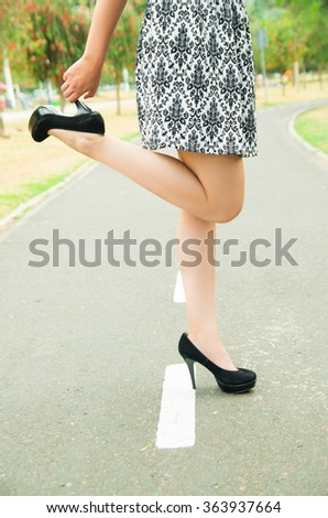 Classy woman wearing fashionable skirt and elegant black high heels bending right knee lifting shoe with hand