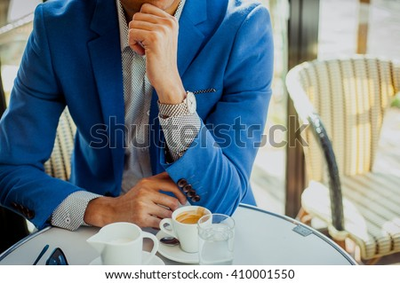 Classy young european businessman in a blue suit in Parisian outdoors cafe - stock photo