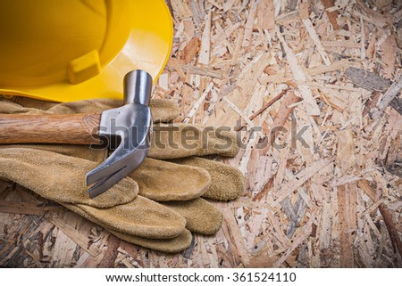 Claw hammer hard hat safety gloves on OSB construction concept. - stock photo