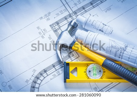 Claw hammer rolls of blueprints construction level building and architecture concept  - stock photo